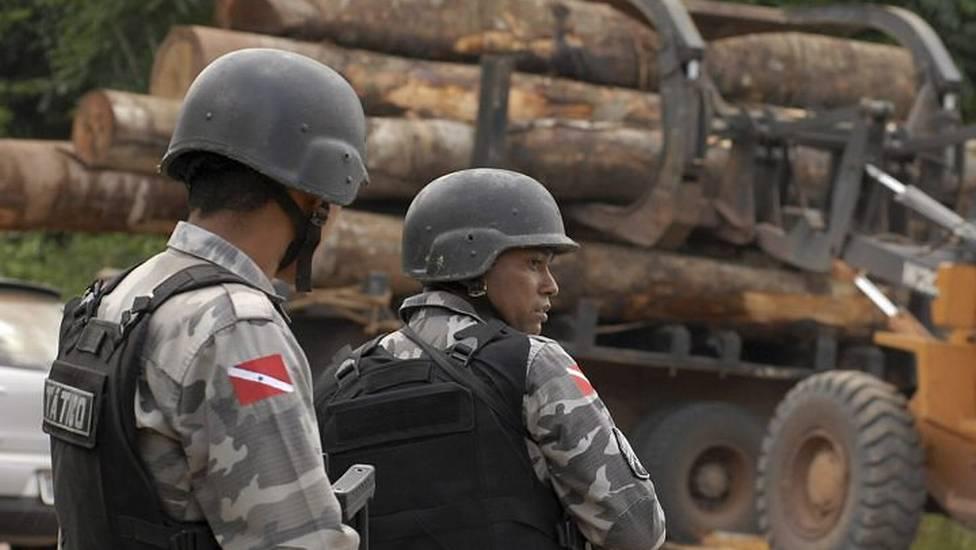 Policiais militares com madeira apreendida em Tailândia/PA. (Foto: Paulo Santos/Reuters)