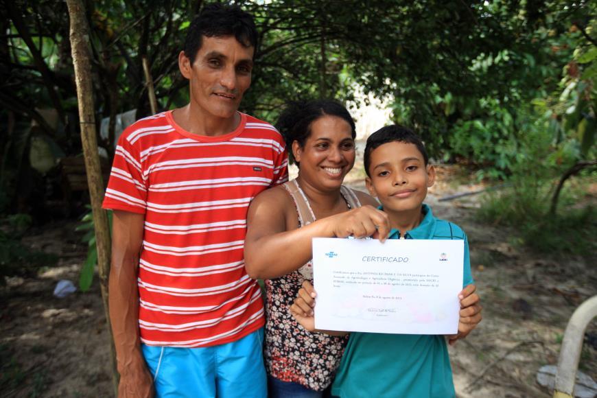 Laércio com o filho e a esposa, Antônia, que mostra a Declaração de Cadastro que atesta que seu produto realmente é orgânico (Foto: MÁCIO FERREIRA/ AG. PARÁ)