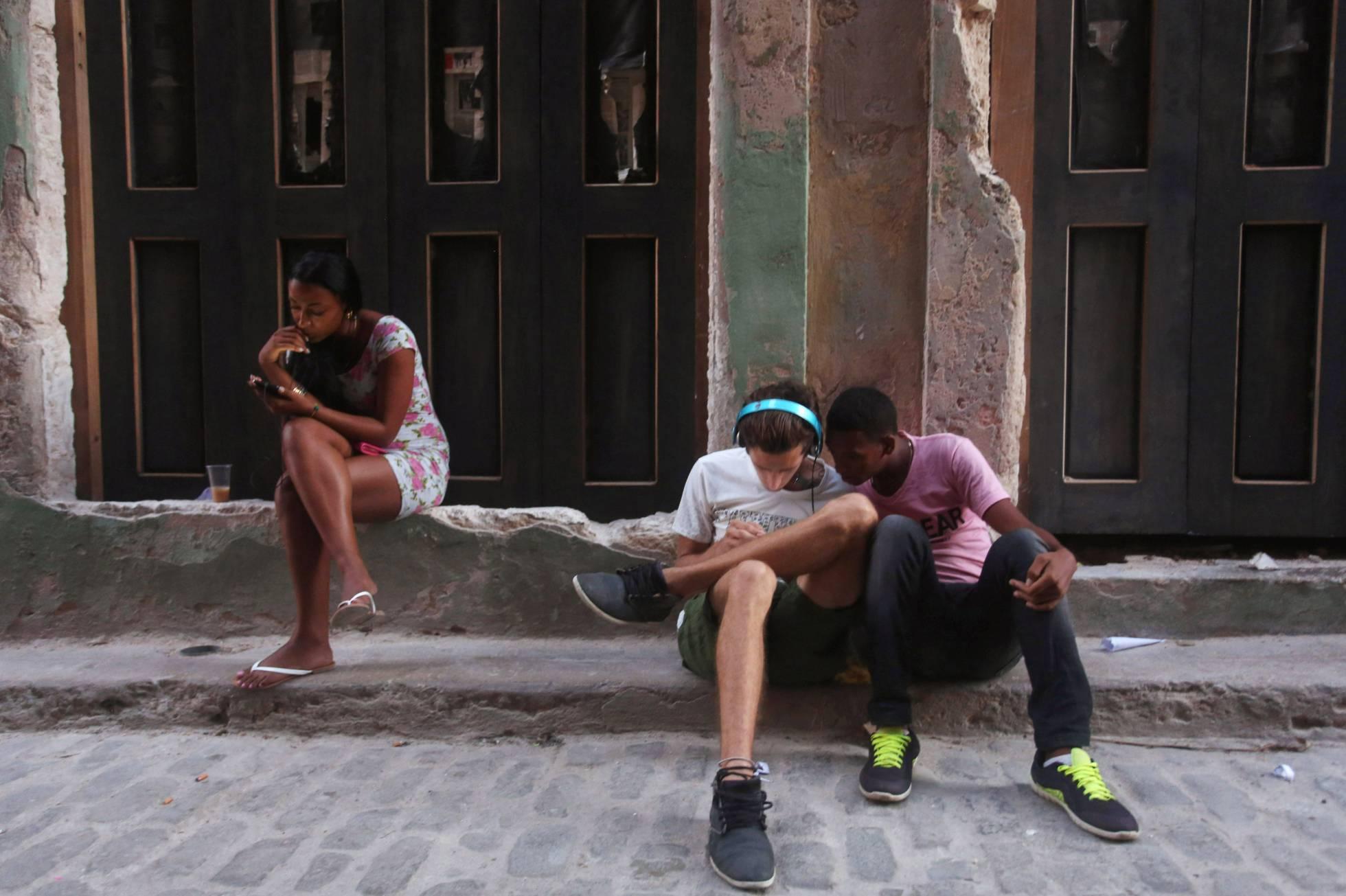 Jovens usam telefones celulares em Havana. (REUTERS)